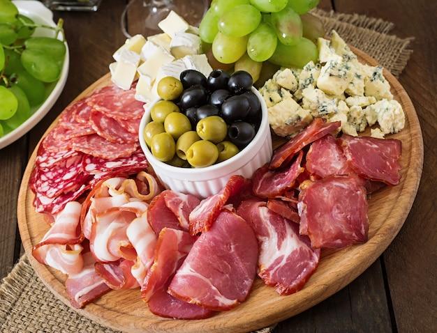 Antipasti catering platte mit speck, trockenfleisch, salami, käse und trauben auf einem holztisch