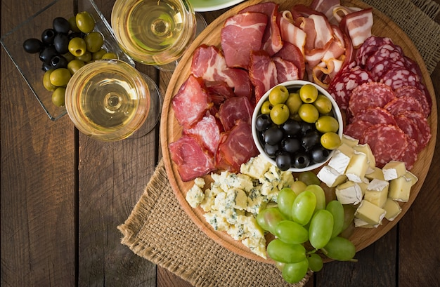 Antipasti-catering-platte mit speck, trockenfleisch, salami, käse und trauben