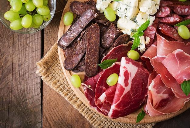 Antipasti catering platte mit speck, trockenfleisch, wurst, blauschimmelkäse und trauben