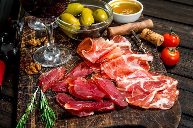 Antipasti hintergrund. verschiedene fleischsnacks mit rotwein. auf einem hölzernen hintergrund.