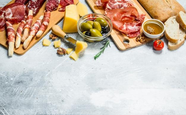 Antipasti hintergrund. vielzahl von italienischen snacks. auf einem rustikalen hintergrund.