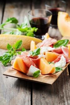 Antipasti mit melone, mozzarella, schinken und basilikum
