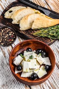 Antipasti-platte mit frischem feta-käse, brot und oliven. weißer holztisch. draufsicht.