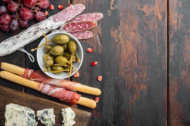Antipasti-platte mit frischkäse, brot und oliven auf dunklem holz, flach gelegt