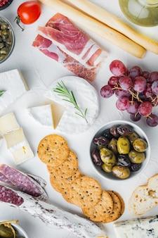 Antipasti-platte mit frischkäse, brot und oliven, auf weißem hintergrund, flach gelegt