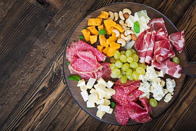 Antipasti-verpflegungsplatte mit speck, trockenfleisch, wurst, blauschimmelkäse und trauben auf einem holztisch. ansicht von oben