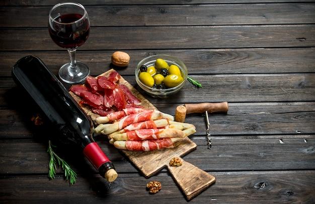 Antipasti. verschiedene fleisch vorspeisen mit oliven, marmelade und rotwein. auf einem holz.