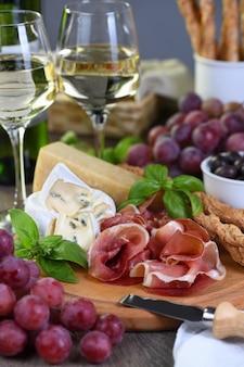 Antipasti. weinset snacks aus getrocknetem schinken, camembertkäse mit schimmel, parmesan mit grissini, oliven und rosa trauben.