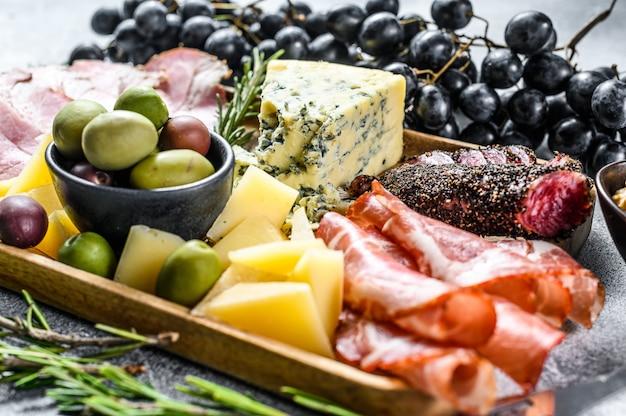 Antipastiplatte mit schinken, schinken, salami, blauschimmelkäse, mozzarella und oliven. ansicht von oben