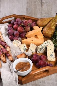 Antipastogericht mit grissini in speck-brie-käse camembert-blauschimmelkäse und weinrebe mit früchten