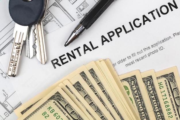 Antragsformular miete. finanzielles konzept. dokument mit hausschlüssel, stift und geld. foto von oben