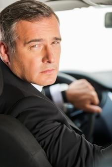 Antrieb verantwortlich. rückansicht eines selbstbewussten reifen geschäftsmannes, der auto fährt und über die schulter schaut