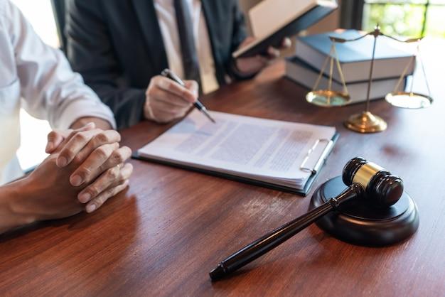 Anwalt, der mit dem mandanten zusammenarbeitet und vertragspapiere mit messingwaage bespricht