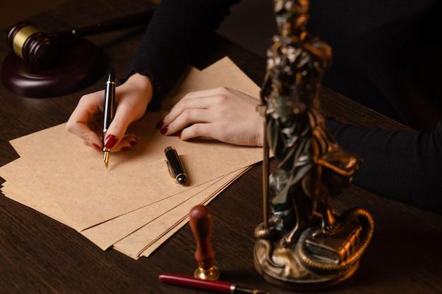 Anwalt, der mit vertragspapieren und hölzernem hammer auf tabel im gerichtssaal und im richter des rechtsanwalts arbeitet