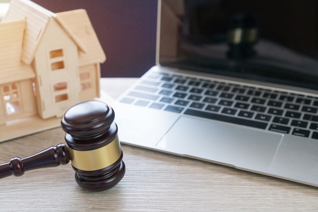 Anwalt für immobilienmakler, wohnungsbaudarlehen oder scheidung. konzept der konfliktklage wegen nichtzahlung von hausschulden, die daher eine gerichtliche verfolgung erfordert. richterhammer mit haus am computer