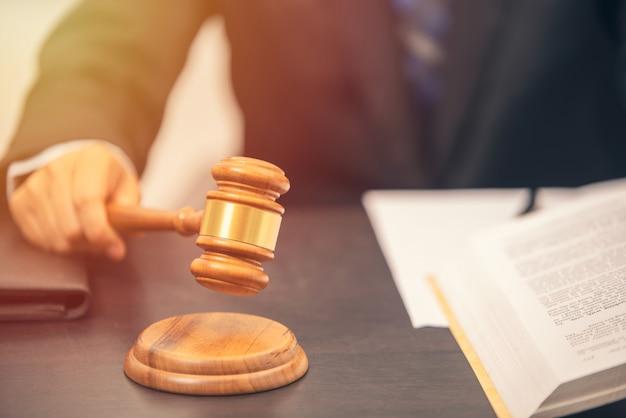 Anwalt hält richterhammer im gerichtssaal, anwaltsrichterkonzept