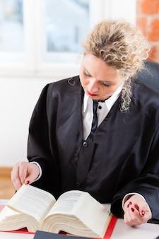 Anwalt im büro liest gesetzbuch