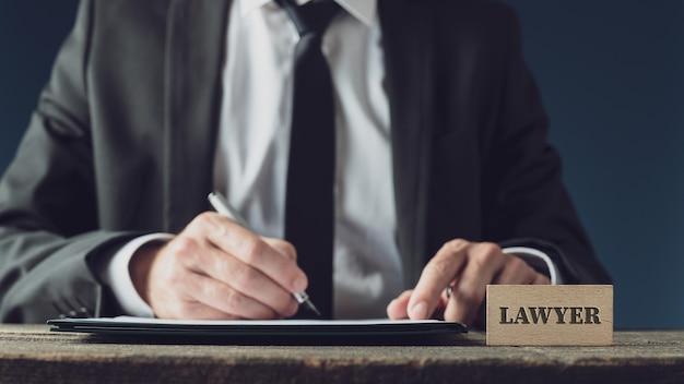 Anwalt sitzt an seinem rustikalen holzschreibtisch und unterschreibt ein juristisches dokument mit einem tintenschreiber.