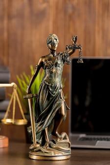 Anwalt und judje konzept. nahaufnahme von themis und laptop auf dem hintergrund.