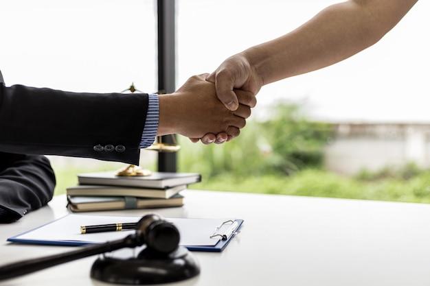 Anwalt und mandant geben sich die hand, nachdem ein rechtsstreit gewonnen wurde, bei dem ein von einem mandant in einem betrugsfall beauftragter anwalt und fair und korrekt vorgegangen wurde, gewinnt der mandant den fall. konzept für betrugsstreitigkeiten.