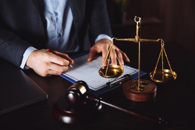 Anwaltsbüro. statue der gerechtigkeit mit waage und anwalt, die an einem laptop arbeiten