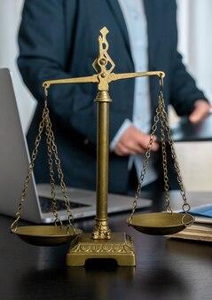 Anwaltskanzlei mit waage, laptop und dokumenten am arbeitsplatz.