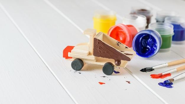 Anwendung der bunten farbigen beschichtung auf dem hölzernen modell des lkw.