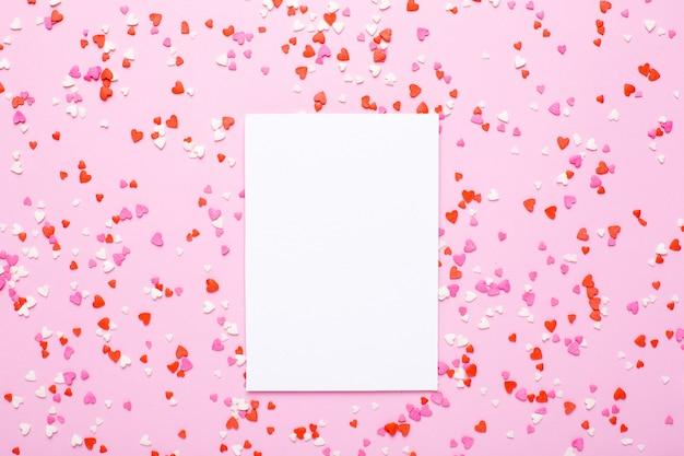 Anwesende karte mit den rosa, roten herzen auf rosa