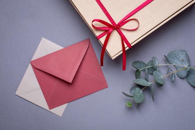 Anwesende karte und geschenk im kasten mit satinband auf grau