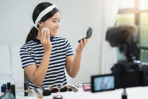 Anwesende schönheitskosmetik des schönheitsbloggers beim sitzen in der vorderen kamera für videoaufzeichnung