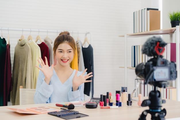 Anwesende schönheitskosmetik des schönheitsbloggers, die in der vorderen kamera für videoaufzeichnung sitzt