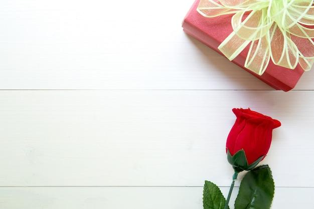 Anwesendes geschenk mit rotrosenblume und geschenkbox mit bogenband auf holztisch