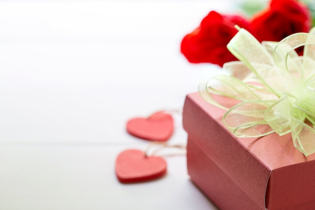 Anwesendes geschenk mit rotrosenblume und geschenkbox mit bogenband und -herzen auf holztisch