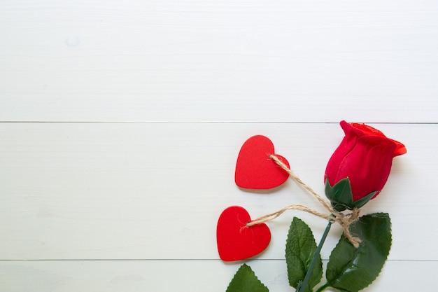 Anwesendes geschenk mit rotrosenblume und herz formen auf holztisch