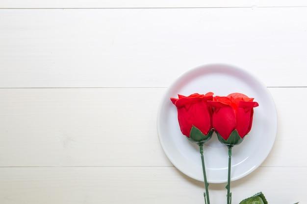 Anwesendes geschenk mit rotrosenblume und -teller auf holztisch