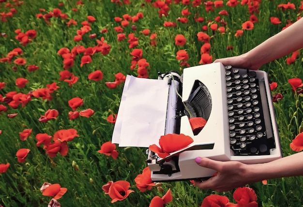 Anzac tag. frühlingsblumen und schreibmaschine mit leerem papier auf blütenfeld. erinnern