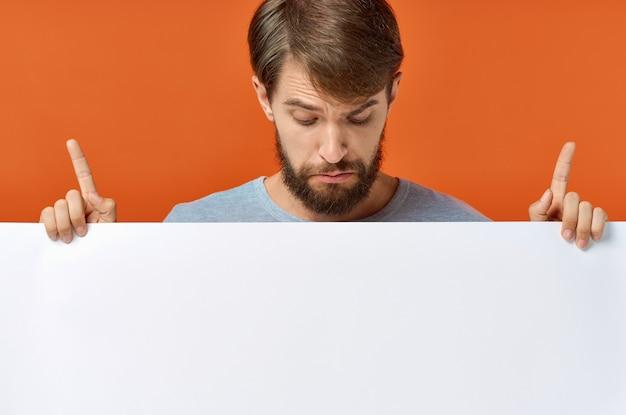 Anzeigenplakat in den händen eines mannes auf einem orangefarbenen hintergrund, der mit seinen händen gestikuliert, raummodell kopieren. hochwertiges foto