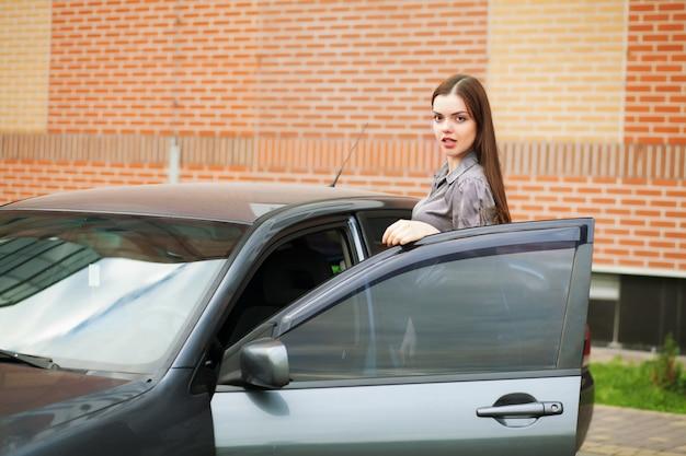 Anziehende junge frau, die das auto und das lächeln fährt