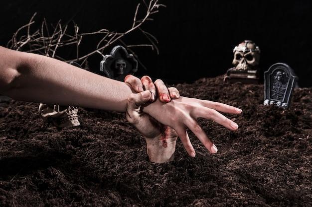Anziehende person der zombiehand an halloween-kirchhof