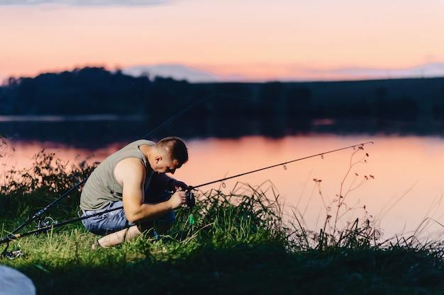 Anziehender karpfen des fischers am see in der sommerzeit am abend