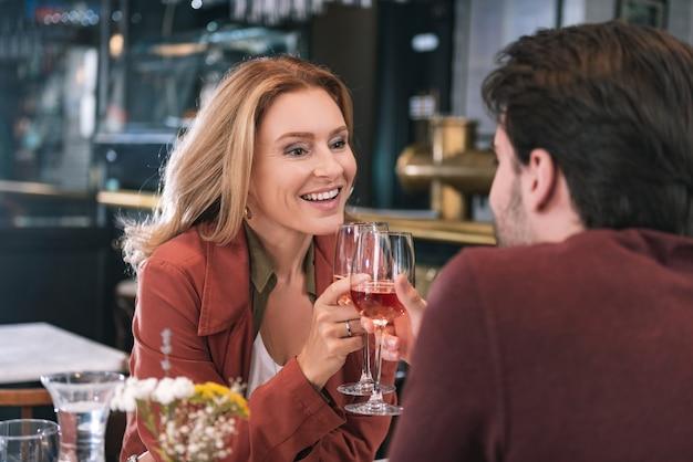 Anziehendes optimistisches paar, das wein trinkt und restaurant besucht