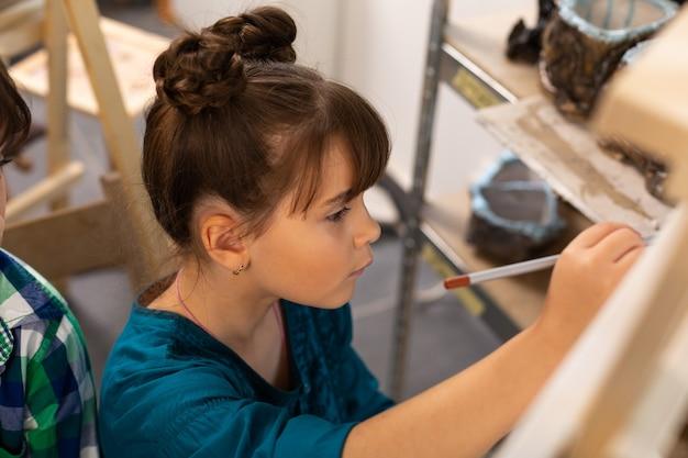 Anziehendes süßes mädchen, das sich beim malen in der kunstschule gut fühlt