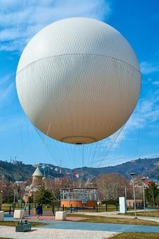 Anziehungsflug in einem großen heißluftballon über der stadt tiflis