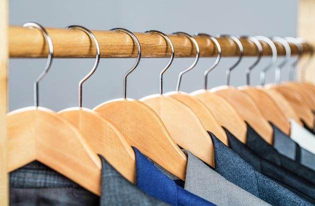 Anzüge für männer, die auf dem regal hängen. herrenanzüge in verschiedenen farben hängenden kleiderbügel