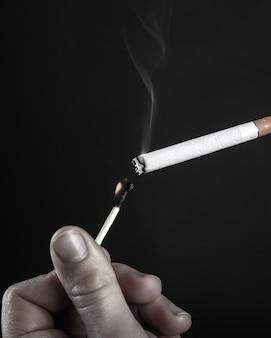 Anzünden einer zigarette mit einem brennenden streichholz in schwarz und weiß.