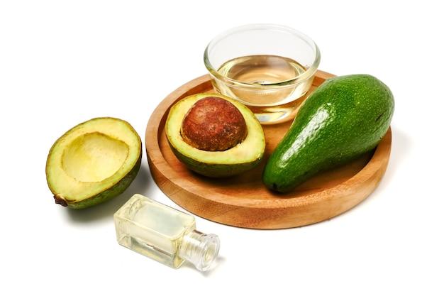 Aocado-öl und frische avocado in der hölzernen platte auf weißem hintergrund