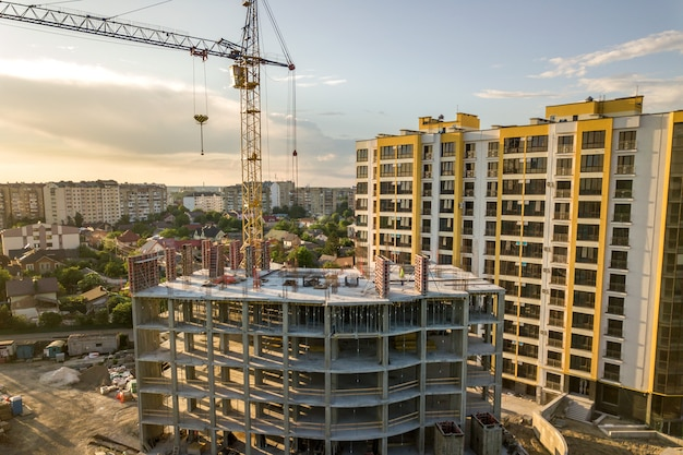 Apartment oder büro hohes gebäude im bau. backsteinmauern, glasfenster, gerüste und betonstützpfeiler. turmkran auf hellblauem himmel kopieren raum