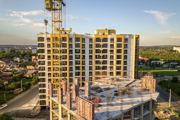 Apartment oder büro hohes gebäude im bau. backsteinmauern, glasfenster, gerüste und betonstützpfeiler. turmkran auf hellblauem himmel kopieren raum.