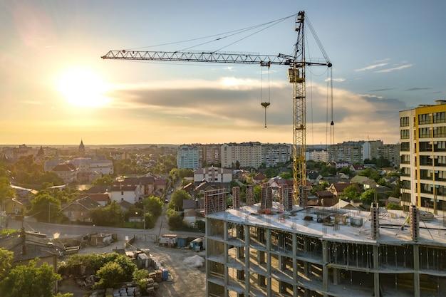 Apartment oder büro hohes gebäude im bau. backsteinmauern, glasfenster, gerüste und betonstützpfeiler. turmkran auf hellblauem himmel kopieren raumhintergrund.