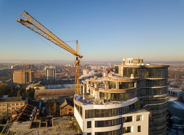 Apartment oder büro hohes gebäude im bau, draufsicht. turmkran auf hellblauem himmel kopieren raum, stadtlandschaft, die sich zum horizont erstreckt. drohnen-luftaufnahmen.